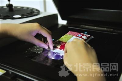 实验人员先用手持X荧光能谱仪检测袋装牛奶包装